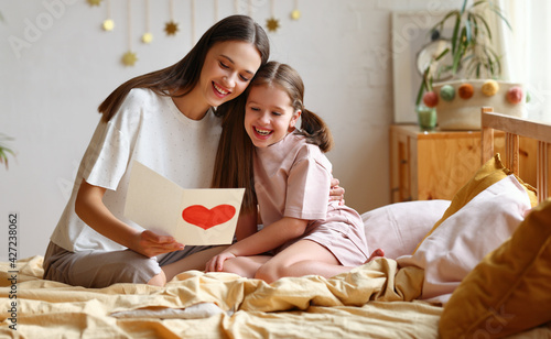 Happy mother and daughter reading greeting card on bed