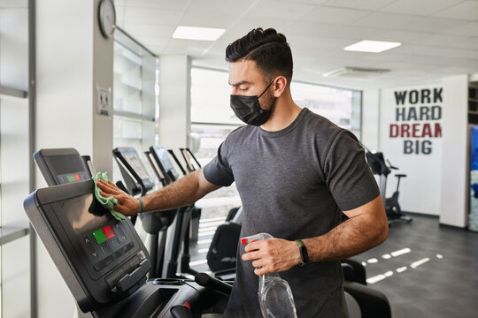 Fit muscular gym guy disinfecting treadmill after workout wearing face mask