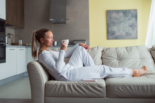 Woman drink coffee lay on sofa at home, white suit, relax, well being , me time concept