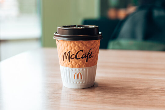 Odessa ,Ukraine - March 05 2021: Paper cup of McDonald's Coffee on a wood table in a cafe