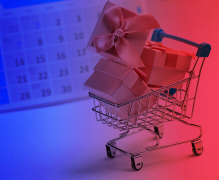 Miniature shopping cart and gift boxes with desktop calendar in neon light. Holiday shopping, black friday, monthly special offer concept