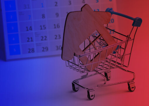 Miniature shopping cart, house figure with desktop calendar in neon light. Holiday shopping, black friday, monthly special offer concept. Home purchase