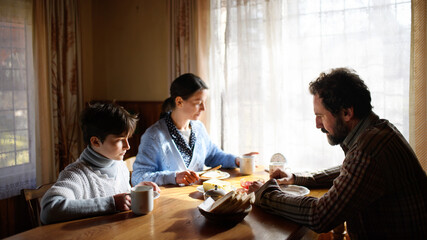 Fototapeta Portrait of poor sad small girl with parents eating indoors at home, poverty concept.