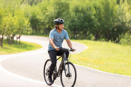 Happy mature man riding bike in park