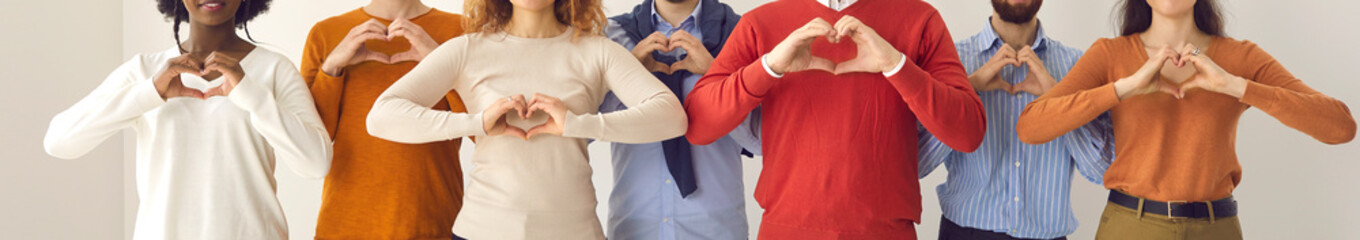 Fototapeta Group of thankful youth and senior citizens showing love and support and sending gratitude. Banner with midsection shot of young and mature people doing heart shape hand gesture