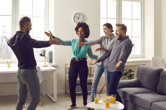 You're finally back. Group of young diverse people excited to meet their friend who's been away for a long time. Happy man spreading arms wide open to hug his friends who he missed so much