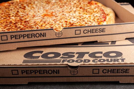 Clarksburg, MD, USA 04-7-2021: Closeup angled image of a carton box of delicious made to order COSTCO cheese pizza. Very popular bargain priced food court item from the wholesale giant.