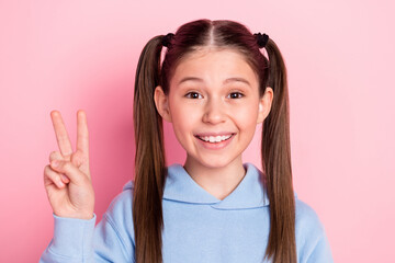Fototapeta Photo portrait of happy schoolgirl showing v-sign gesture smiling in blue outfit isolated on pastel pink color background