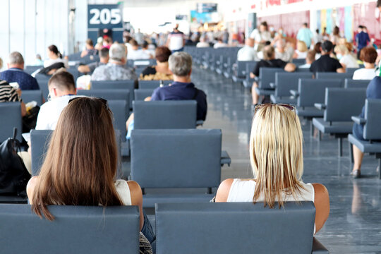 Passengers sitting in the airport terminal. People are waiting for their flight, travel concept