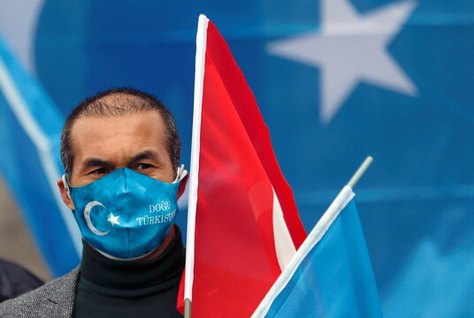 A demonstrator wearing a protective face mask with flag of East Turkestan flag takes part in a protest against China, in Ankara
