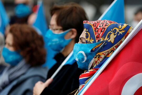 Demonstrators wearing protective face masks with flag of East Turkestan flag take part in a protest against China, in Ankara