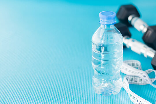 Empty space for the text. A measuring tape, dumbbells, a bottle of water on a sports mat.