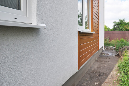 Modern house facade insulation under plastering, stucco and wood wall siding. The combination of stucco and wood siding, wood cladding on the external house wall.