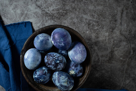 eggs are painted with blueberries in the form of a marble pattern. blue Easter eggs lie in a clay bowl on a stone background.