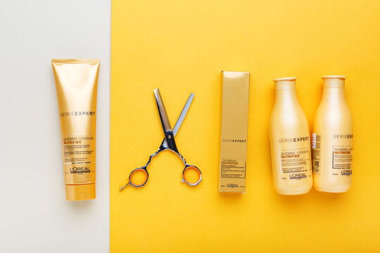 L'oreal professionnel Paris Serie Expert loreal nutrifier hair professional products set hairdressing scissors. Loreal hair shampoo mask on yellow color background. Gold cosmetics bottles. Flat lay