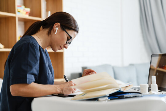 Focused woman doctor using earphone while working with laptop and papers