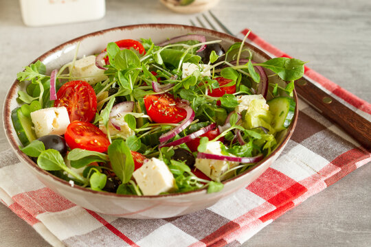 Greek salad of fresh cucumbers, tomatoes, sweet peppers, lettuce, red onion, feta cheese and olives with olive oil.