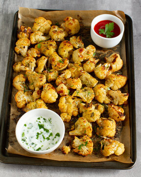 Roasted cauliflower in a tray with different sauces