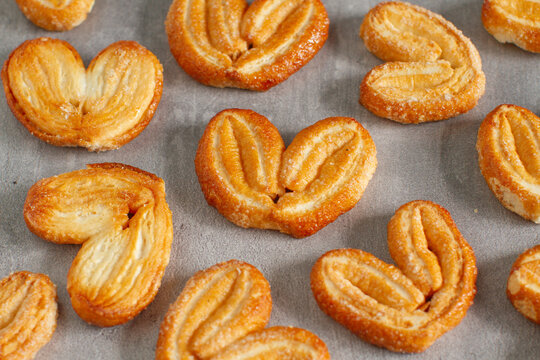 Fresh puff pastry cookies in  shape of a heart. Classic French pastries