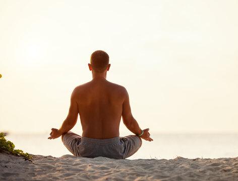 Calm man meditating on beach at sunset