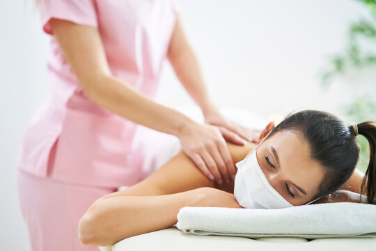 Adult woman in mask during relaxing massage in spa