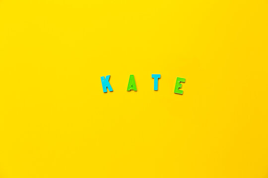 The word Kate made of colored plastic letters with magnets on a yellow background with copy space, text place. Preschool education in a fun color form as a game. A girl name. Banner. English grammar