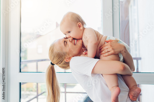 Mother's day. Young mother holding and hugging newborn baby infant son in diaper at home. Family relaxing on balcony.