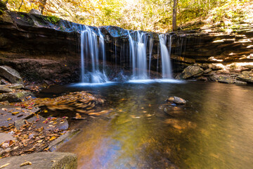 colorful autumn foliage with calming cascading waterfall in Pennsylvania. Wall mural