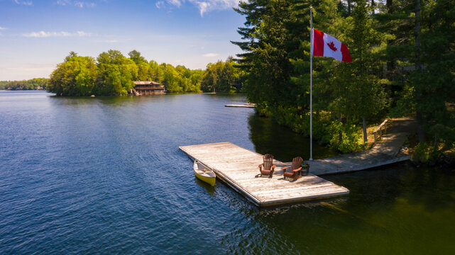 Aerial view of two Adirondack chairs on a wooden dock facing a lake in Muskoka, Ontario Canada. A yellow canoe is tied to the pier where a Canadian flag is flying. A cottage is visible in background.