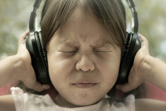 A little kid afraid of loud noise, sensitive to sound, covering ears. Autism and bad sensory processing.
