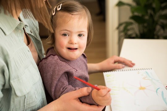 Girl with down syndrome drawing and looking to the camera