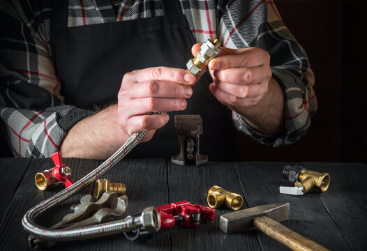 Plumber connects brass fittings to plumbing hose. Close-up of hand of the master during work in workshop