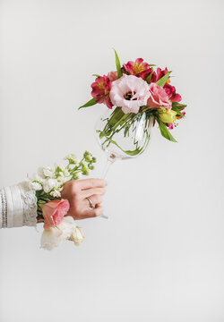 Wine glass full of fresh Spring flowers in female hand