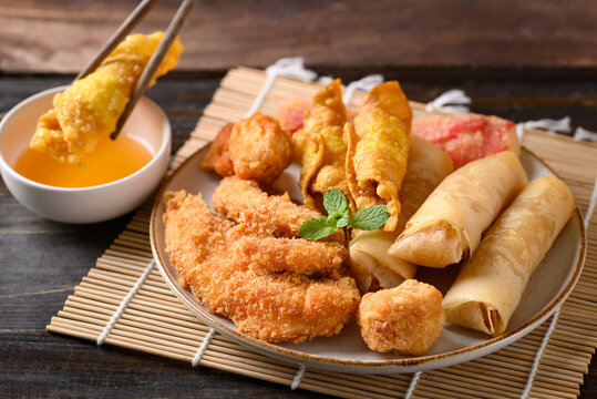 Asian mixed deep fried food (chicken, spring roll, wonton and crab stick) dipping with chili sauce by chopsticks