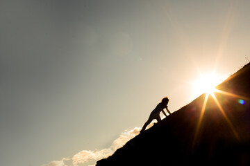 Fototapeta Man climbing a mountain with the sun in the background. Concept of never give up on your goals and dreams obraz
