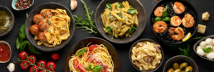 Assortment of Italian pasta with traditional sauces for dinner on dark background.