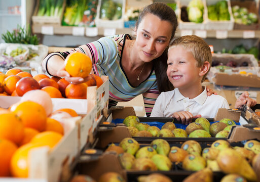 Cheerful brunette mother with little boy buying oranges at store