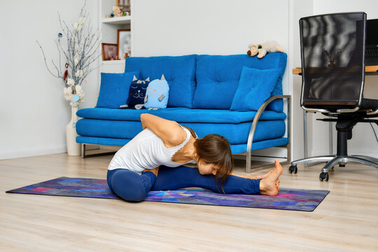 Full length portrait of young woman doing yoga pose on a floor