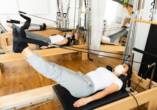 Positive young Latina wearing protective mask to prevent viral infections practicing pilates stretching exercises on reformer at gym.