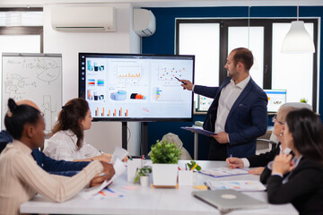 Obraz Manager holding briefing presentation in conference room monitor project. Corporate staff discussing new business application with colleagues looking at screen - fototapety do salonu