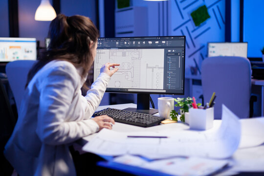 Over the shoulder shot of engineer woman drawing architectural plans and looking at cad software on desktop computer. Designer using arhitecture blueprints of buildings creating industrial prototype