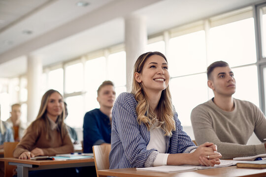 Group of happy college students listening lecture in the classroom.