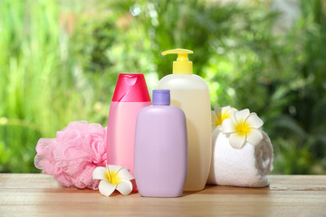 Wall Mural - Different shower gel bottles with towel, mesh pouf and plumeria flowers on wooden table