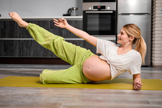 portrait of young caucasian pregnant woman lifting leg up, doing exercises on fitness mat