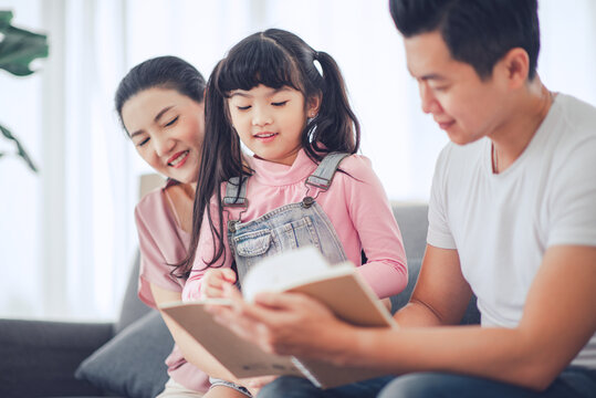 Happy Asian family (mother, father, child daughter) reading a book while smile