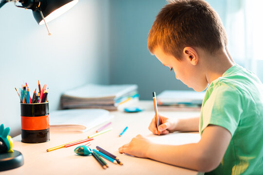 Boy sitting at the desk doing homework at home.