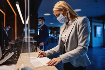Obraz Blond businesswoman with face mask standing at reception in hotel and filling up the form during corona virus pandemic. Business trip, travel during corona, COVID19 precautionary measures - fototapety do salonu