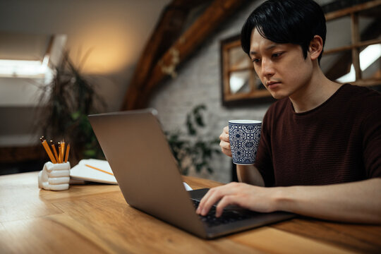 Japanese man drinking coffee and typing on computer.