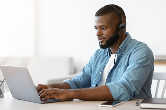 Black millennial man in headset working remotely with laptop at home office