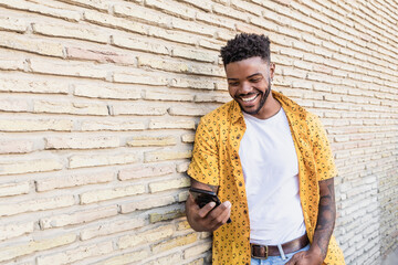 Lifestyle portrait of a handsome american man using a smartphone in the street with brick wall as...